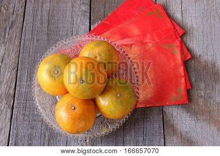 Top view of fresh oranges in a bowl on old wooden board with Chinese red envelope packet or ang pao background. Happy Chinese new year concept.