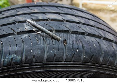 Screw Puncturing Tire, flat tire on white background.