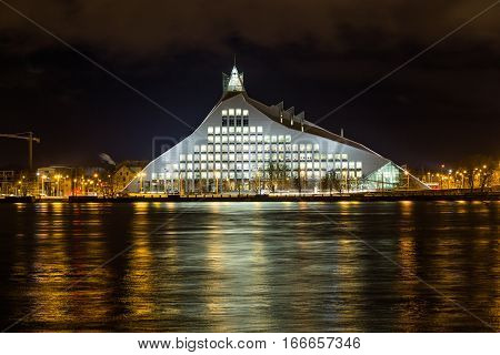 RIGA LATVIA - 2ND JAN 2017: TRIGA LATVIA - 2ND JAN 2017: The National Library of Latvia at night from across the Daugava River