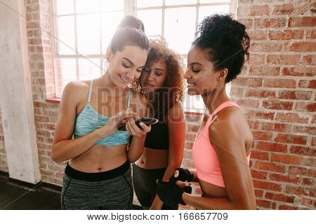 Group Of Girls In Fitness Class Looking At Smartphone