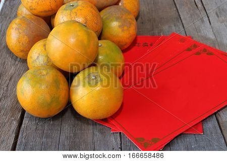 Stack of fresh oranges with Chinese red envelope packet or ang pao on old wooden board background. Happy Chinese new year concept.