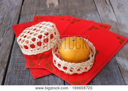Orange in a basket on old wooden board with Chinese red envelope packet or ang pao background. Happy Chinese new year concept.