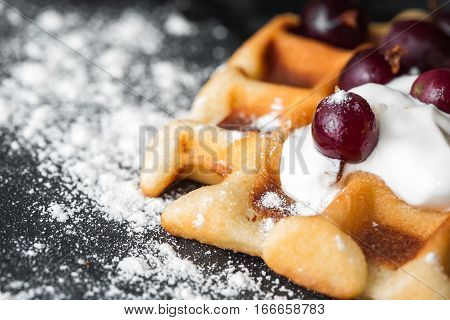 traditional homemade Belgian waffles with berries, whipped cream and powdered sugar on dark background. rustic style