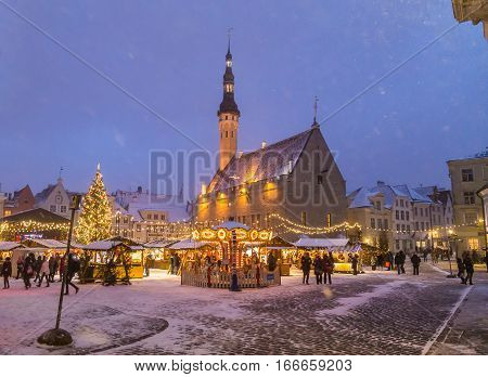 TALLINN ESTONIA - 4TH JAN 2017: Raekoja plats Old Town Hall Square in Tallinn at night during the festive period. Christmas decorations market stalls and people can be seen.