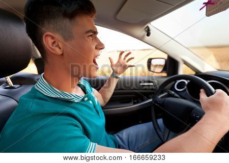 Portrait of a Furious Young Man in a Car