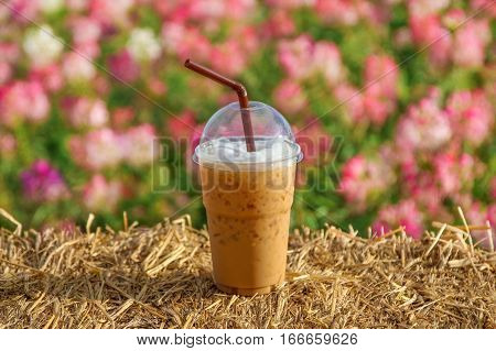 A cup of iced coffee on rice straw bales with flower  background.