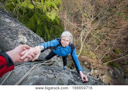 Male Rockclimber Is Helping A Climber Female