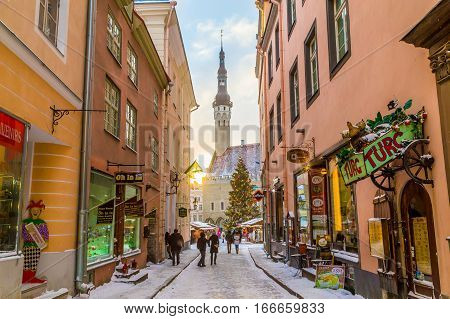TALLINN ESTONIA - 5TH JAN 2017: Raekoja plats Old Town Hall Square in Tallinn in the morning during the festive period. Christmas decorations market stalls and people can be seen.