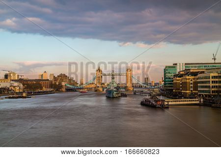 LONDON UK - 11TH MARCH 2015: A view towards Tower Bridge at sunrise across the River Thames. HMS Belfast can be seen in front of it.