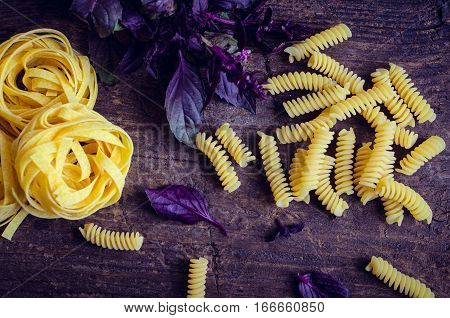 Fusilli and tagliatelle with fresh purple basil on old rustic wooden background. Traditional Italian pasta. Top view.