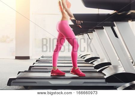 Side view of attractive young unrecognizable woman in pink leggings running on treadmill in gym. Female slim legs jogging in fitness club. Healthy lifestyle concept