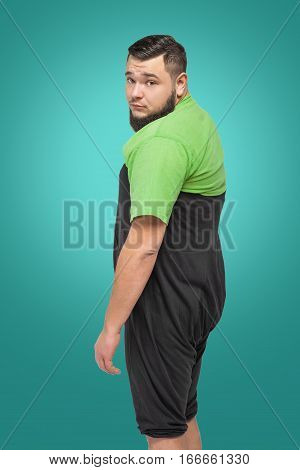 tired upset man in green shirt and black pants over turquoise background