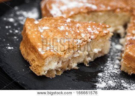 homemade appetizing Apple pie with powdered sugar on dark Board