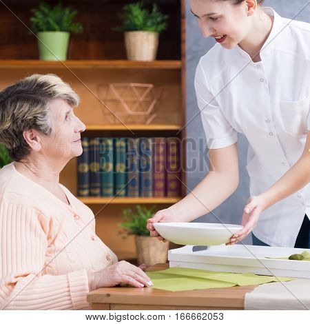 Caregiver Serving Soup To Senior Lady