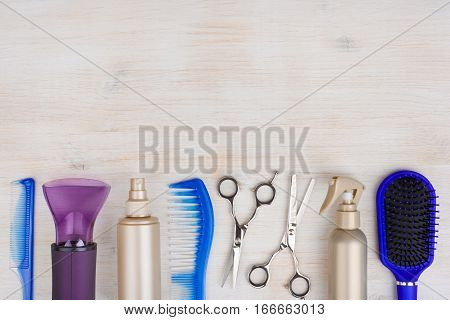 Professional hairdresser tools on wooden surface with copyspace at top