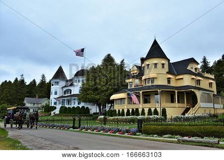 MACKINAC ISLAND, MI. - JULY, 2016:  A horse and carriage in front of the famous west bluff cottages on Mackinac Island.