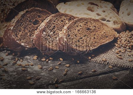Plenty of sliced bread background. Bakery and grocery concept. Fresh, healthy whole grain sliced sorts of rye and white loaves, sprinkled flour on sackcloth and rustic wood table, food closeup.