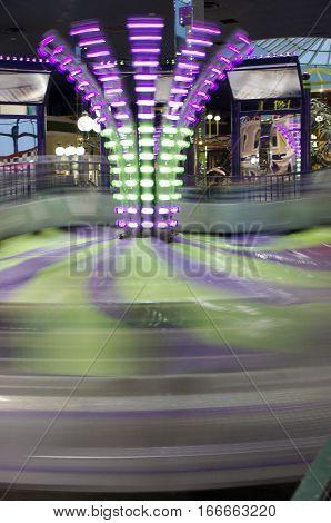 tall green and purple carnival ride blur