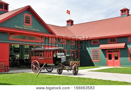 MACKINAC ISLAND, MI - JULY 2016: Exterior of the antique carriage museum with a passenger vehicle parked outside.