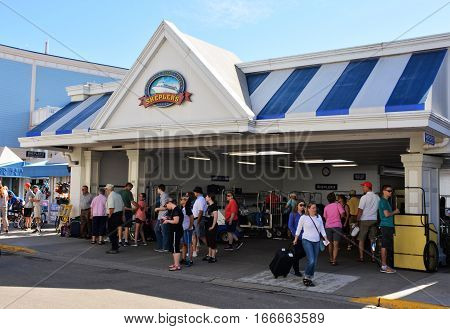 MACKINAC ISLAND, MI - JULY, 2016: Passengers arriving at the Sheplers ferry terminal now look for a horse drawn taxi to their hotel.