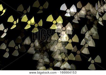 golden yellow white hazard ionizing radiation warning symbol on a dark black background