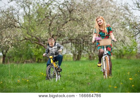Mother with son riding bicycles against the background of blooming fresh greenery in spring garden. Female wearing flowered dress and yellow shoes