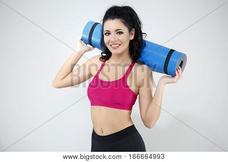 Portrait Of Happy Young Woman Holding Rolled Up Exercise Mat Over Gray Background.