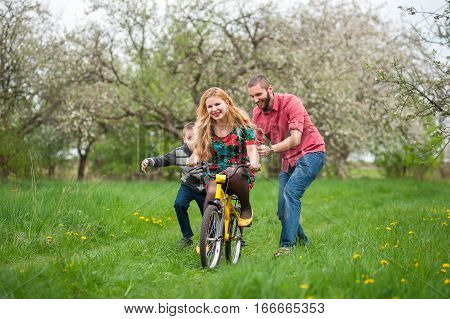 Mother Teaching Son To Ride A Bike By His Example