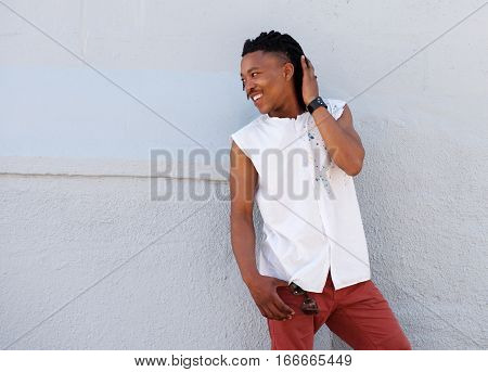Young Man With Dreadlocks Smiling Outside Against Gray Wall