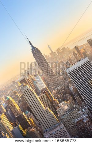New York City. Manhattan downtown skyline with illuminated Empire State Building and skyscrapers at sunset seen from Top of the Rock observation deck. Vertical composition.