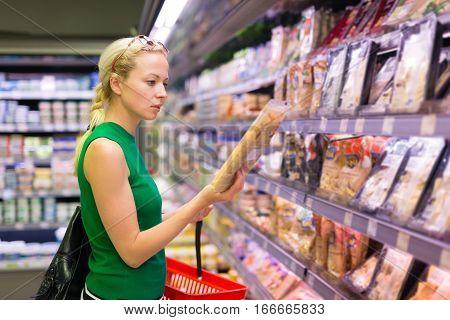 Beautiful caucasian woman shopping groceries at supermarket.