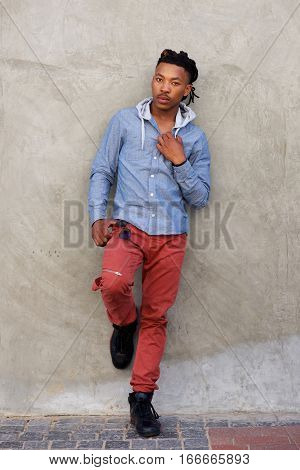 Full Length Cool African Man With Dreadlocks Leaning Against Wall
