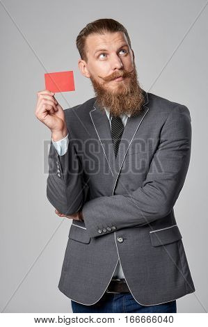 Hipster business man with beard and mustashes in suit standing over grey background holding credit card looking up