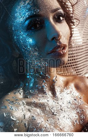 portrait of a girl with glitter on her cheek pierced nose lies on the shiny fabric