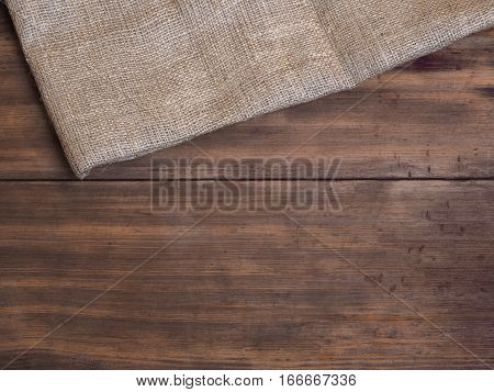 Arrangement of old wooden boards and burlap vintage background, photo top view. Burlap hessian sacking texture on wooden table background. Copy space for text.