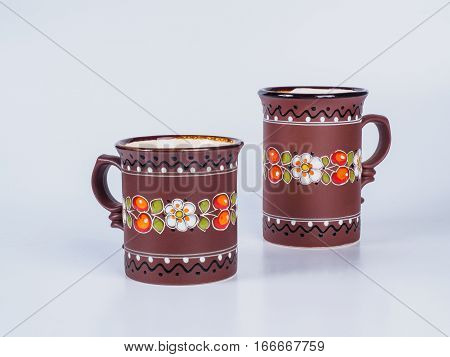 Close up on two brown tea cups decorated with designs isolated on white background. Handmade earthenware. Side view.