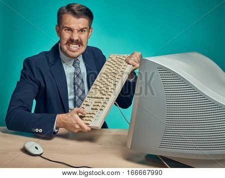 Angry fury businessman breaking keyboard against a blue studio background