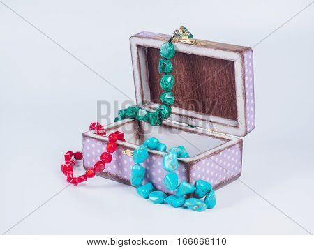 Picture of the opened purple-coloured box for bijouterie with turquoise, malachite and coral bead necklaces isolated on white background. Handmade decoupage jewel box. Side view.