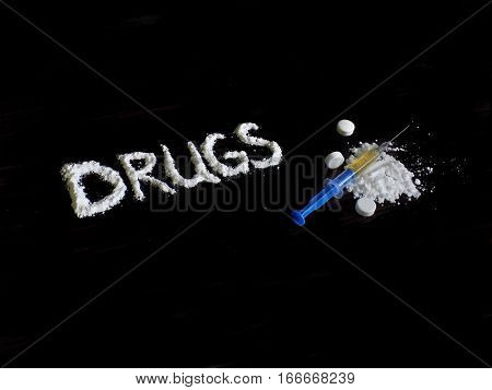 Cocaine drug powder in drugs word shaped, pills and injection syringe on cocaine pile on black background