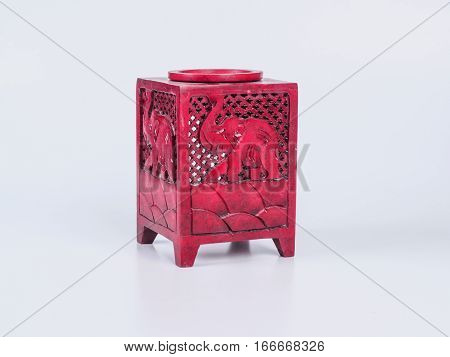 Picture of a red aroma lamp on white background. Aroma lamp made of stone. Elephant carved on aroma lamp.