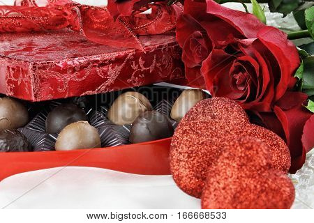 Heart shaped box of Valentines Day chocolates with beautiful long stem red roses. Selective focus on candy and flowers with extreme shallow depth of field.