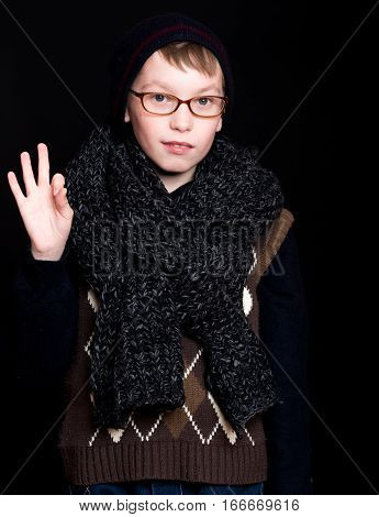 small boy or cute nerd kid in glasses hat and fashionable knitted scarf on black background holds ok gesture