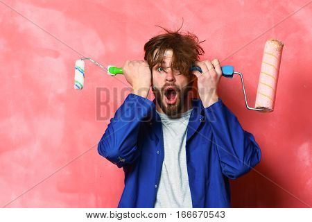 Surprised Man Holding Paint Rollers