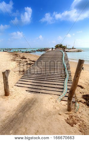 The wooden bridge which goes to sea with turquoise water. The bridge is located on a sandy beach of Thailand.