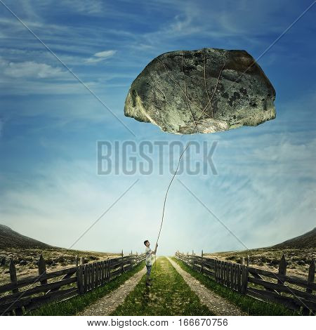 Surrealistic image as a young boy stand on a country road holding a rope bound around a huge stone as a playing kite. Life pressure stress and hard determination concept.