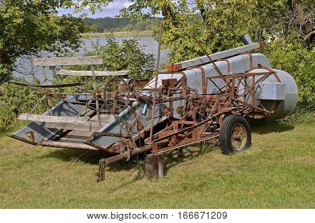 An old rusty power takeoff combine is parked in the grass along a lake