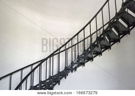 A black wrought iron spiral staircase ascends the interior of the historic Bodie Island Lighthouse at Cape Hatteras National Seashore on the Outer Banks of North Carolina.