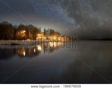 Riverside street lights and starry sky are reflected in the river