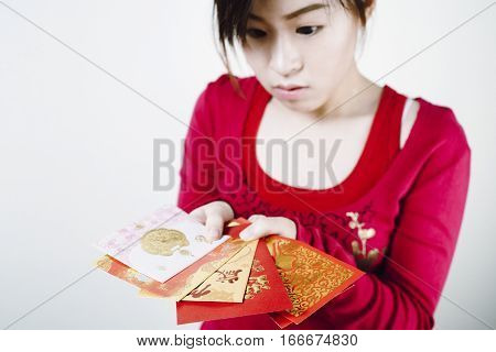 Asian girl look curious with Red packets in her hands for Chinese New Year Gifts Traditional Celebration Chinese New Year. Selective focused on red packets.