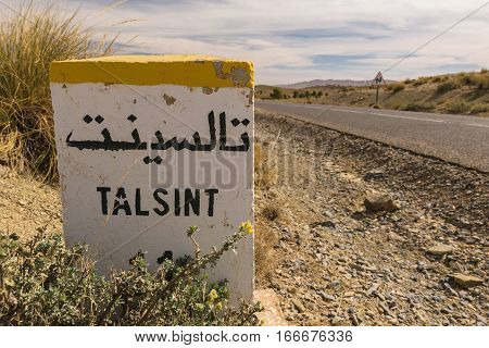 A kilometer stone with Arabic characters on it saying Talsint, Morocco.